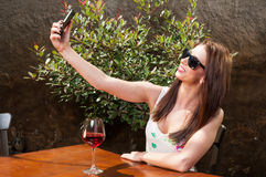 Girl wearing shades and drinking wine taking selfie. Outside on terrace in a sunny day Stock Image