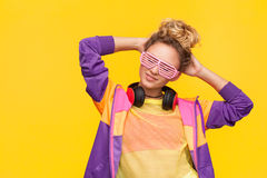 Girl wearing shutter glasses and casual dress. Blonde woman with hair bun wearing shutter glasses and purple jacket posing standing against yellow background Royalty Free Stock Image