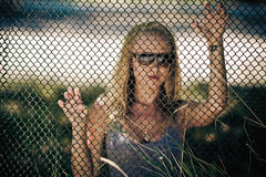 Girl wearing spectacles behind a lattice Stock Photos
