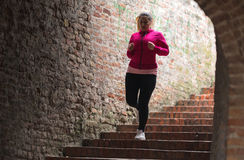 Girl wearing sportswear and running down stairs at city fortress Stock Photos