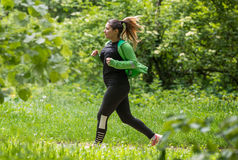 Girl wearing sportswear and running in forest at mountain. Pretty girl wearing sportswear and running in green forest at mountain during spring stock image