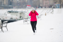 Girl wearing sportswear and running on snow during winter Royalty Free Stock Photography