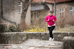 Girl wearing sportswear and running upstairs at city fortress Stock Photos