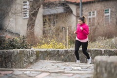 Girl wearing sportswear and running upstairs at city fortress Stock Photo
