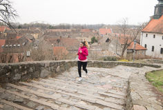 Girl wearing sportswear and running upstairs at city fortress Royalty Free Stock Photography