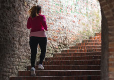 Girl wearing sportswear and running upstairs at city fortress Royalty Free Stock Photos