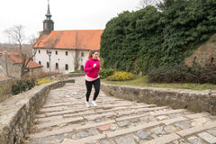 Girl wearing sportswear and running upstairs at city fortress Stock Photography