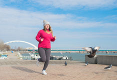Girl wearing sportswear and running on windy day. Pretty girl wearing sportswear and running on windy day at quay Stock Images