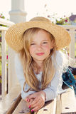 Girl wearing straw hat. Close up portrait of a cute little girl wearing a straw hat in the garden stock image