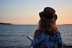 Girl wearing a straw hat is standing by the sea stock photo