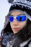 Girl wearing sun glasses. Beautiful girl posing in the snow Royalty Free Stock Image