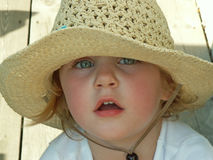 Girl wearing sun hat. Girl shading eyes from the sun with a big floppy hat royalty free stock photography