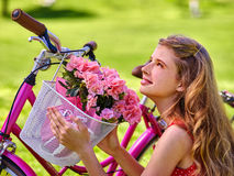 Girl wearing sundress rides bicycle with flowers basket. Royalty Free Stock Image