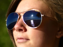 Girl wearing sunglasses. Portrait of young girl wearing sunglasses reflecting sunlight and rippled ocean Stock Photos