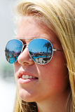 Girl wearing sunglasses. Portrait of a girl wearing sunglasses, reflecting a pool area in a resort Royalty Free Stock Images