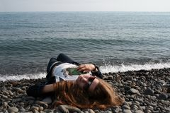 A girl wearing sunglasses lies on a pebble beach Royalty Free Stock Image