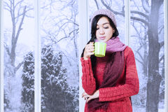 Girl wearing sweater and blow warm drink Royalty Free Stock Image