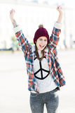 Girl wearing a sweater with peace sign. Attractive young woman outdoors, smiling Royalty Free Stock Photo