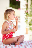 Girl Wearing Swimming Costume Blowing Bubbles. Sitting In Garden Royalty Free Stock Photography