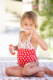 Girl Wearing Swimming Costume Blowing Bubbles. Sitting In Garden Royalty Free Stock Photo