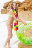 Girl is wearing swimsuit with green rubber ring Stock Photography