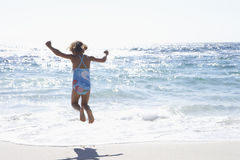 Girl (3-5) wearing swimsuit, jumping above surf on sandy beach, rear view, sea shimmering in sunlight Royalty Free Stock Image