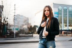 Girl wearing t-shirt and leather jacket posing against street , urban clothing style royalty free stock image