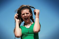 Girl wearing too loud earphone Stock Images