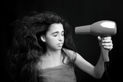 Girl wearing a towel drying her hair with a hairdryer Royalty Free Stock Images