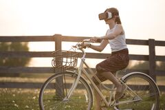 Girl Wearing Vr Box Driving Bicycle during Golden Hour Stock Photos