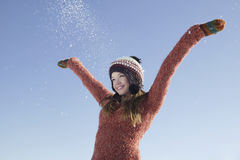 Girl Wearing Warm Clothing With Arms Outstretched In Snow Stock Image