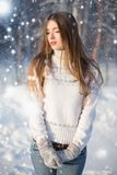 A Girl Wearing Warm Winter Clothes And Hat Blowing Snow In Winter Forest, horizontal.  royalty free stock image