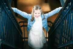 Girl Wearing White Dress and Blue Denim Jacket Standing on Stairs stock image