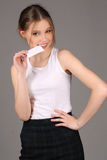 Girl wearing white singlet and bitting card. Close up. Gray background Stock Photography