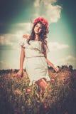 Girl wearing white summer dress in poppy filed. Beautiful girl wearing white summer dress and flower chaplet in poppy filed Royalty Free Stock Photos