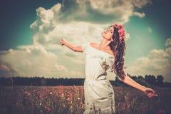Girl wearing white summer dress in poppy filed Stock Images
