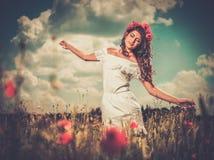 Girl wearing white summer dress in poppy filed Stock Image