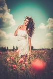 Girl wearing white summer dress in poppy filed Royalty Free Stock Images