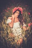 Girl wearing white summer dress in poppy filed Stock Photography