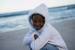 Girl (8-10) wearing white top with hood, crouching on beach at sunset, smiling, portrait (tilt) Royalty Free Stock Image