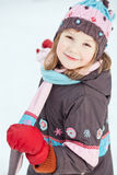 Girl wearing winter clothes against snowy background Royalty Free Stock Photos