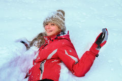 Girl wearing winter clothes lying in  snow Royalty Free Stock Photo