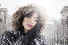 Girl wearing winter jacket with beauty pose. Portrait of beautiful teenage girl wearing winter jacket with beauty pose in snowy day at the city Royalty Free Stock Photo