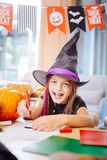 Girl wearing wizard Halloween costume laughing while drawing scary pictures. Laughing and drawing. Blue-eyed girl wearing wizard Halloween costume laughing while stock photo