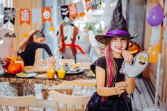 Girl wearing wizard hat feeling excited attending scary Halloween party royalty free stock photos