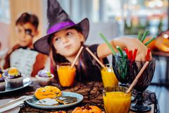 Girl wearing wizard hat for Halloween drinking juice and eating gummy sweets royalty free stock image