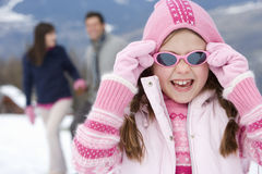 Girl (7-9) wearing woolen hat and sunglasses in snow, smiling, portrait, parents in background stock photo