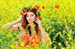 Girl wearing wreath. Redhead girl with crown from field'd flowers Royalty Free Stock Photo