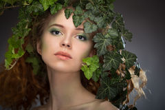 Girl wearing a wreath of ivy leaves. Beautiful girl wearing a wreath of ivy leaves Stock Photo