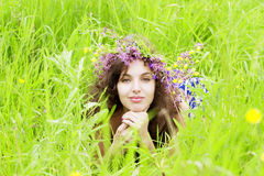 Girl wearing a wreath of wild flowers in the field Royalty Free Stock Photo